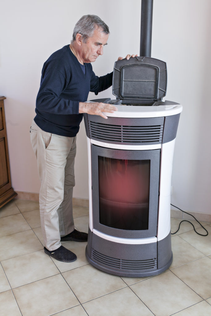 man looking in a pellet stove